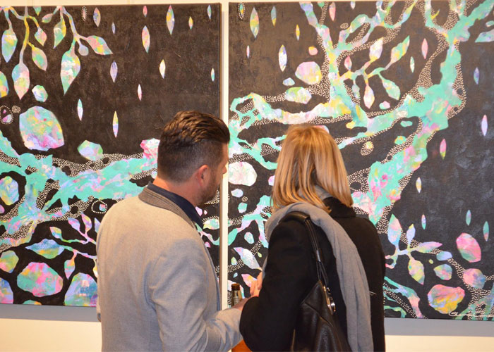 Guests examining Sherren Comensoli's Painting